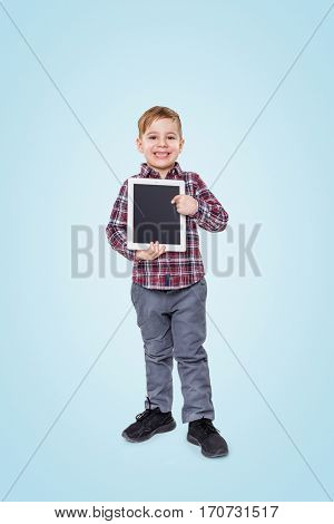 Full length portrait of a cheerful little boy holding and pointing finger at tablet computer isolated over blue background
