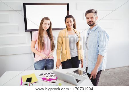 Portrait of confident young editors in meeting room at creative office
