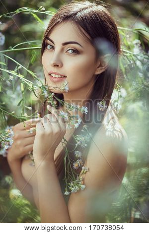 Beautiful young naked woman portrait in flower meadow smiling and looking at camera. No clothes, naked tender girl in the blossoming bushes on spring.