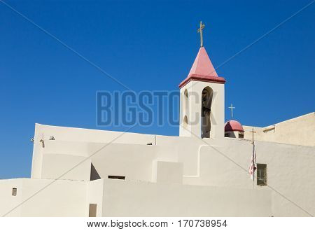 Christian Church in Acre Israel. The white walls and red bell tower on blue sky background