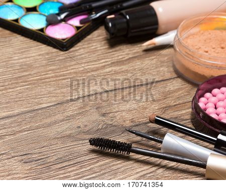 Makeup products frame on wooden surface with copy space: mascara, liquid eyeliner, eyeshadow, blush, powder, concealer, foundation. Shallow depth of field