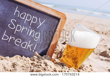 closeup of a wooden-framed chalkboard with the text happy spring break written in it, and a glass of refreshing beer, on the sand of a beach