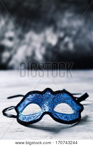 an elegant blue and black carnival mask on a rustic wooden surface