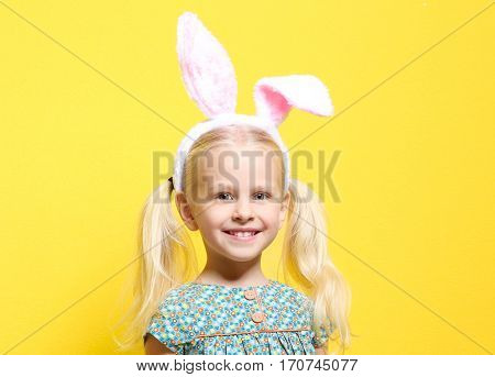 Cute little girl with bunny ears and chocolate rabbit on color background