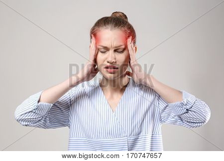 Young woman suffering from head ache on gray background. Health care concept