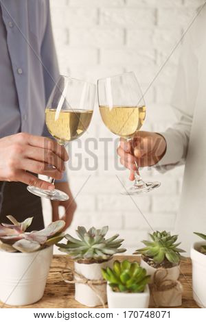 People toasting with glasses of white wine, closeup