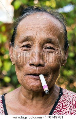 HPA-AN, MYANMAR - JANUARY 21, 2017 : An elderly woman of a Karen tribe is smoking a local cigarette in Hpa-an, Myanmar