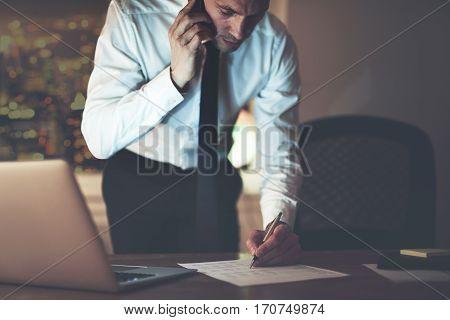 Businessman On Phone Signing Document