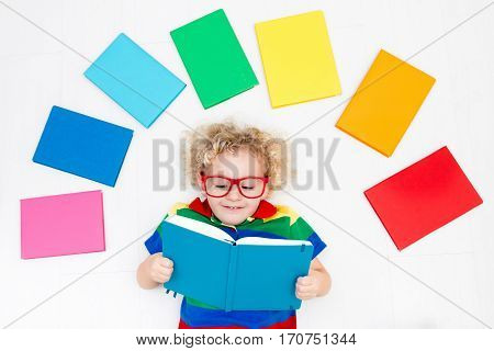 Little boy with colorful rainbow books. Happy back to school student. Child reading and doing homework. Preschooler kids learn and read a book. Curly funny kid in elementary school or kindergarten.