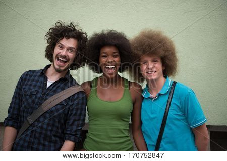 Portrait of multiethnic group of happy three friends in casual wear standing and laughing