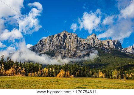 Auroral sunny day in Canmore. Concept of hiking. The famous Three Sisters mountains in the Canadian Rockies  of Canada