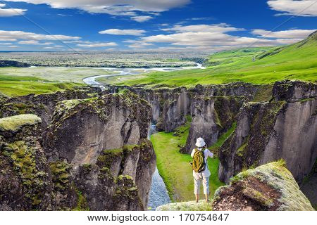 The elderly woman standing on a rock and photographing the landscape. The striking canyon Fyadrarglyufur in Iceland. Green Tundra in summer. The concept of active northern tourism