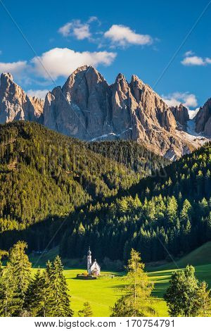 Sunny day in Dolomites, Tirol.  The symbol of the valley Val di Funes - church of Santa Maddalena. Rocky peaks and forested mountains surrounded by green Alpine meadows