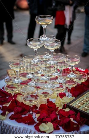 pyramid of glasses with champagne and rose petals on the table