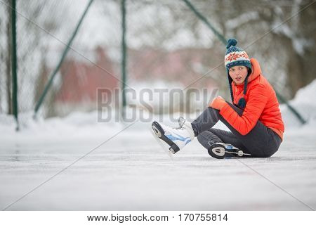 Ice skating concept - young woman sitting on the ice rink after falling down and hurting her knee