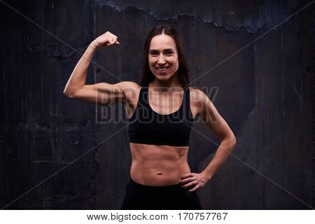 Close-up of fitness sporty girl showing her well trained biceps against black background. Muscular young athlete, light and shade emphasizing the perfect relief of healthy strong body