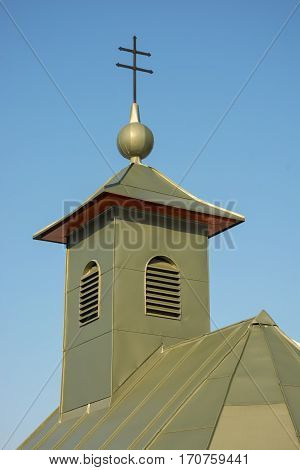 Detail of roof of chapel. Green building against clear blue sky