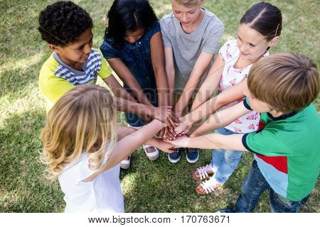 Children putting their hands together in park