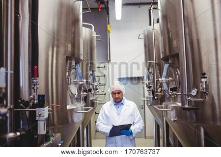 Front view of manufacturer writing while standing amidst storage tanks at brewery