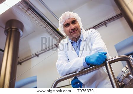 Low angle portrait of smiling manufacturer leaning on pipe at brewery