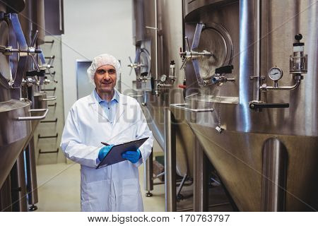 Portrait of smiling manufacturer writing while standing amidst storage tanks at brewery