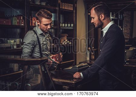 Confident man buying hair care accessories in barber shop
