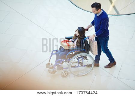 Caregiver shopping with his disabled daughter