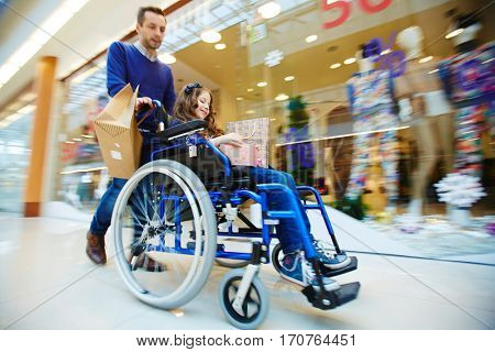 Man and his daughter in wheelchair shopping together during sale