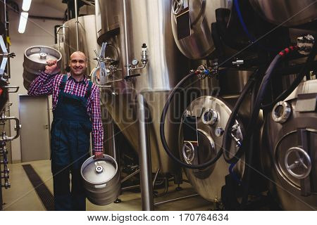 Portrait of brewery worker carrying kegs at factory