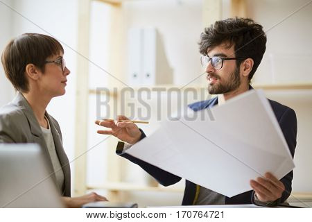 Portrait of bearded creative man holding heap of paper gesturing actively while explaining project details to businesswoman sitting next to him in modern office