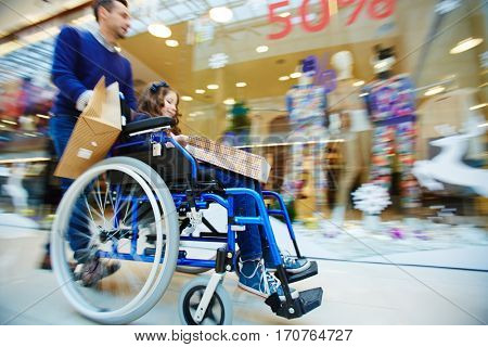 Man pushing wheelchair with daughter in shopping-center