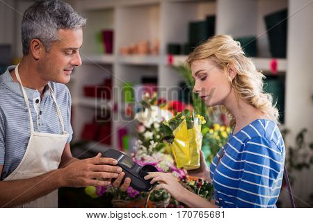 Woman making payment with her credit card to florist in the shop