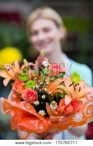 Female florist holding flower bouquet in flower shop