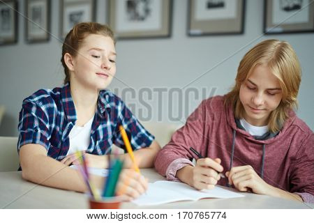 Two classmates making notes during lesson