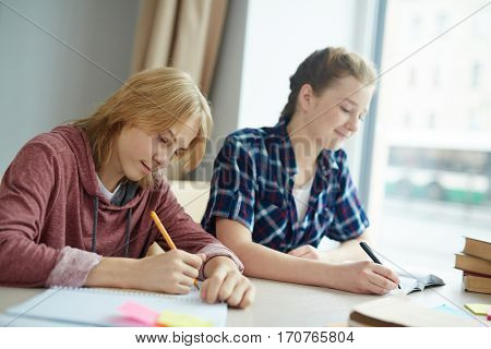 Teenage guy and girl writing essay at lesson