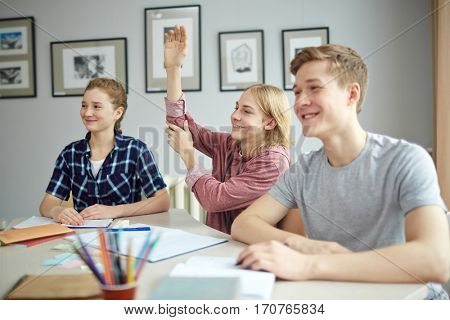 Guy raising hand between his groupmates at lesson