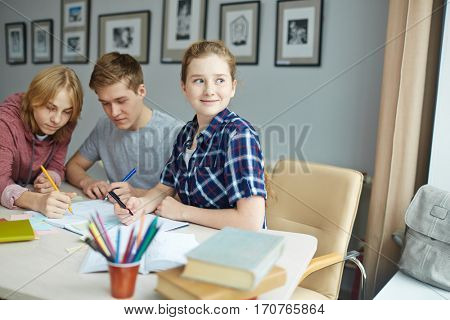 Inspired girl looking aside with two guys carrying out task on background