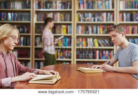Clever students reading books in college library