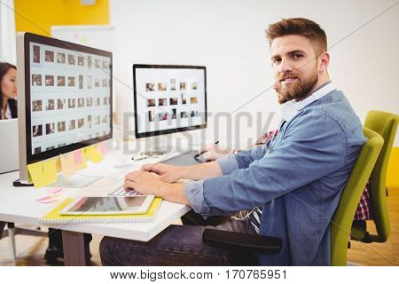 Portrait of confident young male editor working in creative office