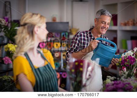 Smiling florist watering flowers in flower shop