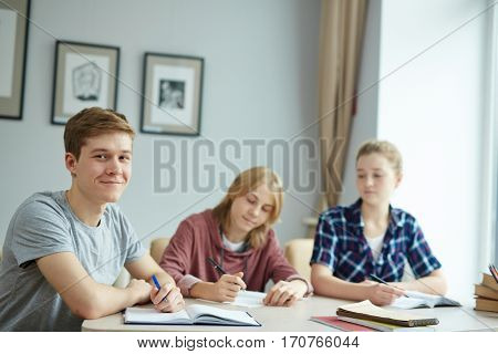 Adolescent guy looking at camera by desk