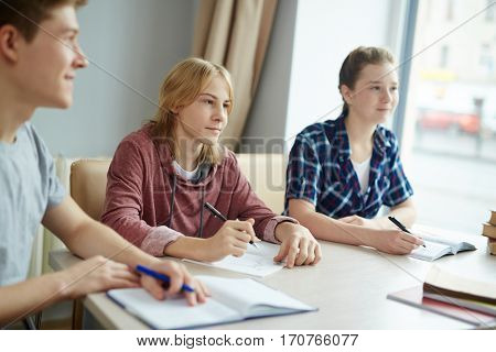 Group of students describing something at lesson