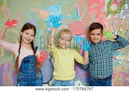 Kids with colorful palms standing against creative wall