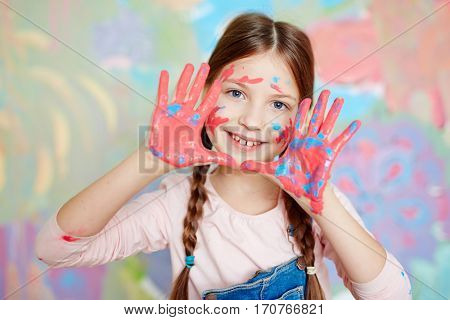 Girl with colorful palms looking at camera