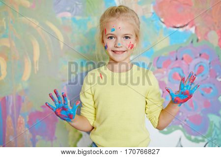 Creative youngster with paints on her palms and face