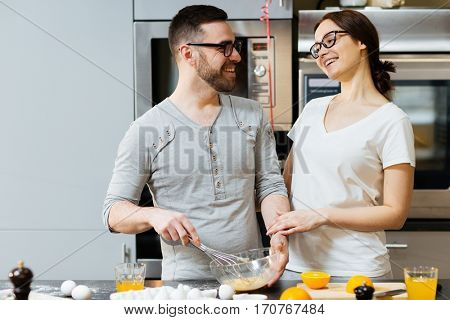 Affectionate couple looking at one another in the kitchen while cooking