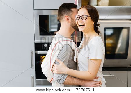 Affectionate spouses embracing at home