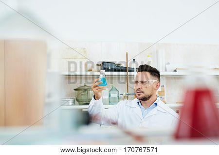 Chemist investigating new substance in tube