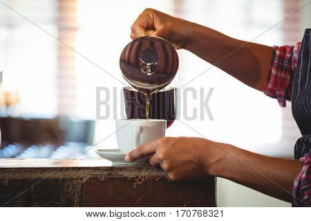 Waitress preparing a coffee in a cafe