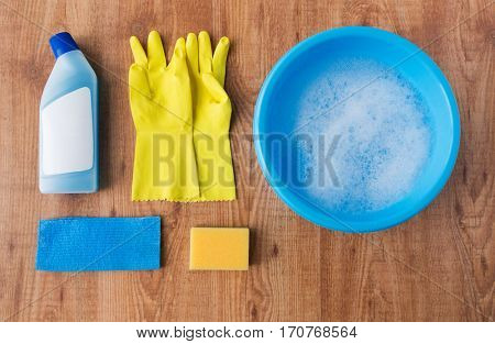 housework, housekeeping and household concept - basin with cleaning stuff on wooden background